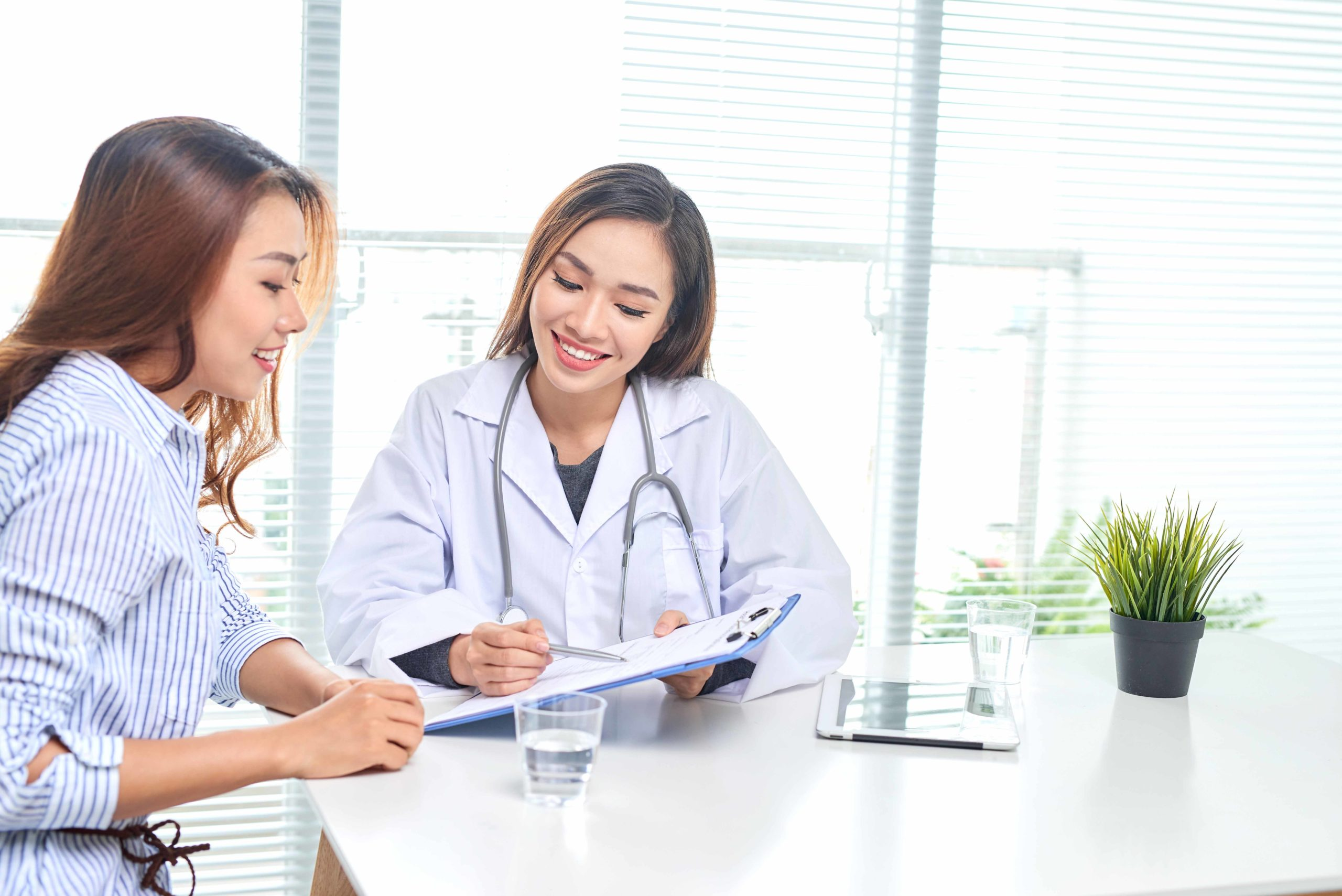 Female doctor talks to female patient in hospital office while writing on the patients health record on the table. Healthcare and medical service.