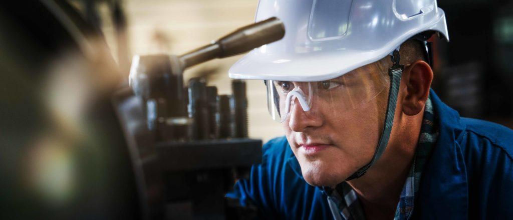 industrial background of caucasian mechanics engineer operating lathe machine for metalwork in metal work factory