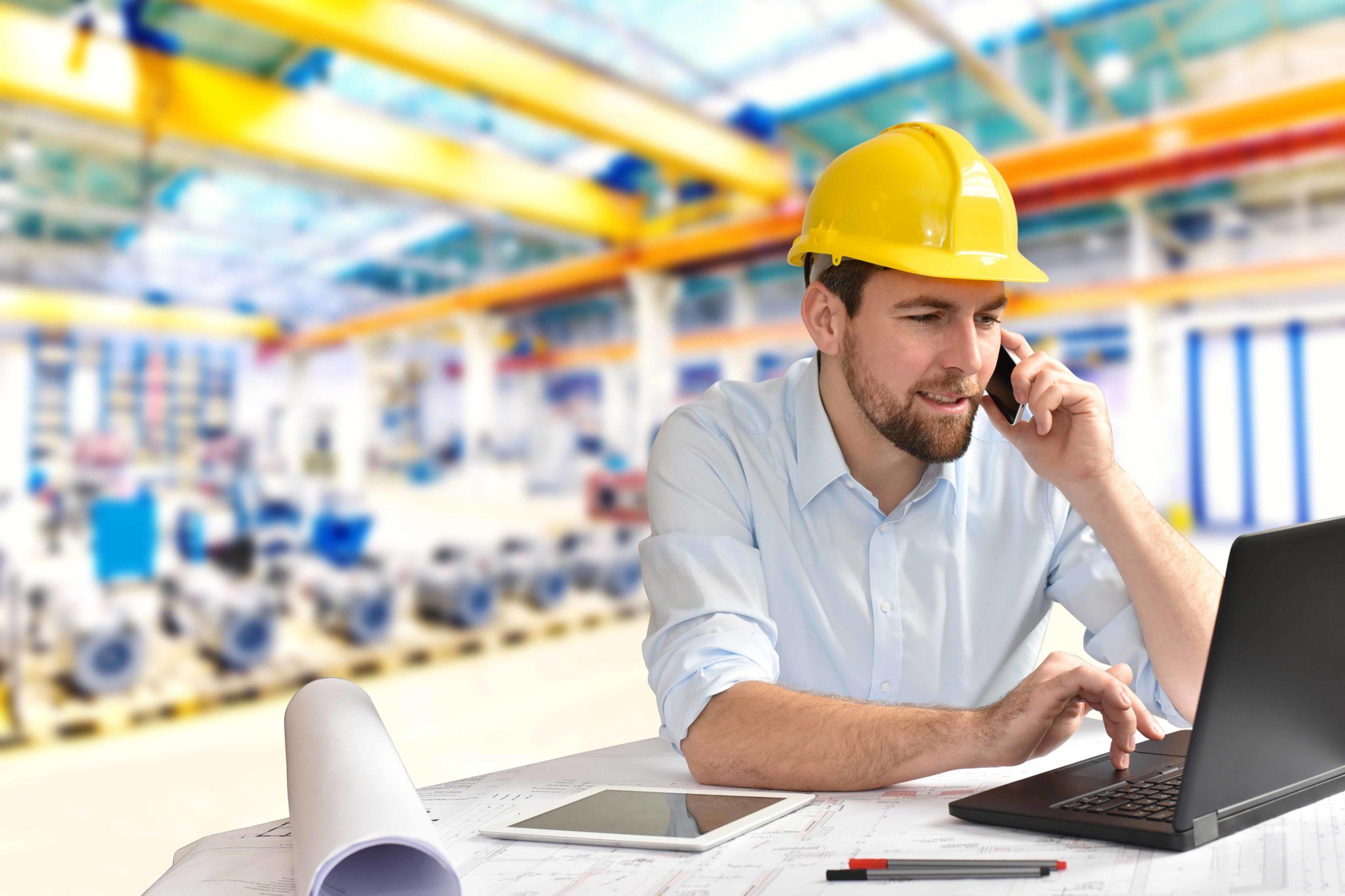 Ingenieur im Maschinenbau telefoniert am Arbeitsplatz/ Schreibti